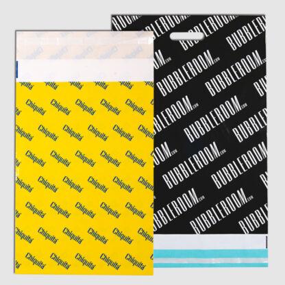 två e-handelspåsar med tryck. Den ena är svart och har stansat handtag och den andra är tryckt gul